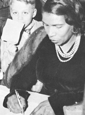 """African American singer Marian Anderson signs autographs for children after her Feb. 6, 1958, performance at Goshen College. That night she stayed at the Hotel Elkhart. Victor Stoltzfus, then a seminary student and a future president of Goshen College, said, """"I asked why an artist of the stature of Marian Anderson would not be welcome in a Goshen motel or hotel."""" — Photo by Goshen College Maple Leaf"""