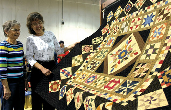 The 50th anniversary commemorative wall hanging, quilted by Charlotte Swope, left, and pieced by Carolyn Bontrager, went for $5,100 Oct. 1 at the Virginia Mennonite Relief Sale. — Jim Bishop for MWR
