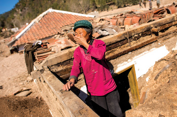 Bong-Suk Shin, 65, looks through what remains of her home for anything she can salvage. She and her grandson lost all their belongings when flooding and landslides ravaged Hamgyong province. — John Lehmann/MCC