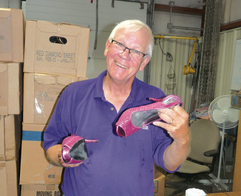 Rod Franz of Manhattan, Kan., holds a pair of donated shoes at the MCC Central States Material Resource Center. — Carol Duerksen for MWR