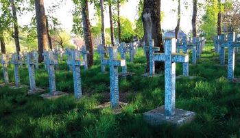 Rows of crosses mark a World War II German military memorial beside 19th-century Orthodox church in the village of Broniki, Ukraine. — Olga Dyatlik