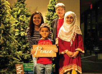 Lidia Bernaldez, back left, and Mount Joy Mennonite Church member Pamela Brubaker stand with Nicolás Bernaldez, front left, and Noor Syed. The friends attended an international Christmas feast hosted by Mount Joy Mennonite Church on Dec. 3. — Chad Houck/EMM