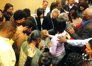Hope for the Future participants pray for Glen Guyton after the announcement of his appointment as Mennonite Church USA's next executive director. — Marco Guete/MCUSA