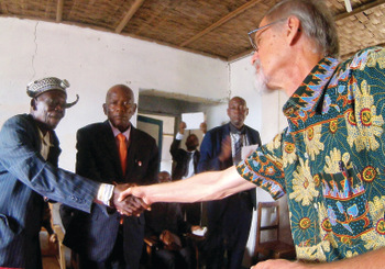 A local dignitary shakes Rod Hollinger-Janzen's hand during the ceremony of confession and reconciliation in Kandale, Congo. Overseeing the greeting is Mennonite Church elder André Ndjoko, one of the event organizers. — Charles Buller/MMN