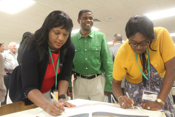 Alicia Manning, left, of the African American Mennonite Association, and Grace Pam of the African Belizean Caribbean Mennonite Mission Association sign a memory book for Ervin Stutzman, who is retiring as executive director of Mennonite Church USA, as Femi Fatunmbi of the ABCMMA looks on. — Alex Woodring/MC USA