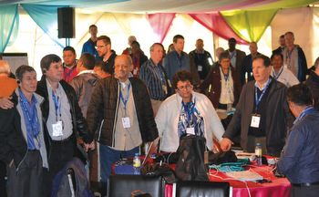"""Delegates join hands as they sing """"We Are One in the Spirit"""" during the Mennonite World Conference General Council meeting in Kenya. — Wilhelm Unger/MWC"""