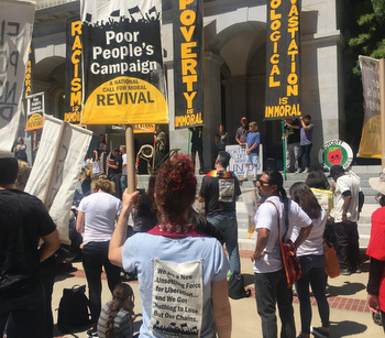 Joanna Shenk, associate pastor of First Mennonite Church of San Francisco, holds a sign May 14 at the Poor People's Campaign in Sacramento, Calif. — Eric Lawrence