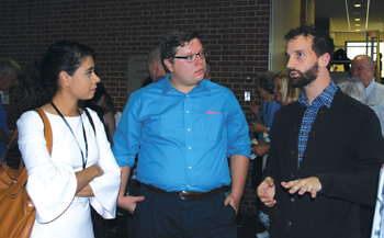 """Sarah Haider, left, founder of an organization that supports former Muslims, and Nic Stoltzfus listen to Stephen Zook between sessions at Amish Heritage Foundation's """"Disrupting History: Reclaiming Our Amish Story"""" conference Sept. 28-29 at Franklin & Marshall College in Lancaster, Pa. — Amish Heritage Foundation"""