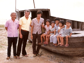 """Victor Neumann, MCC representative in Songkhla, Thailand, with Vietnamese """"boat people"""" in 1979. Mothers of children shown here were abducted by pirates. MCC was the first agency to sign a private sponsorship agreement with the government of Canada, leading hundreds of Mennonite congregations to sponsor thousands of refugees and dozens of church bodies to sign virtually identical agreements. — Mennonite Central Committee"""