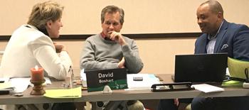 Mennonite Church USA moderator-elect Joy Sutter, moderator David Boshart and executive director Glen Guyton converse at the MC USA Executive Board meeting in Kansas City, Mo. — Janie Beck Kreider/MC USA