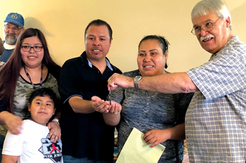 Astrid, Francisco Jr., Francisco and Lorena Flores Sanchez accept the keys to their new home from Carl Dube of MDS. — John Longhurst/MDS