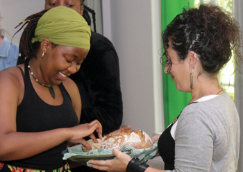 Mima Moyo of Spain, left, receives communion from Nohemy Ruth García of Spain. — Menno's Global Village
