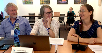 Katie Geddert, right, MCC country co-representative in Ukraine, speaks June 19 at the joint meeting of the U.S. and Canadian MCC boards. At left are MCC Canada board chair Paul Gilbert and MCC U.S. board chair Gwen White. — Paul Schrag/MWR