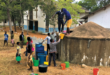 Nyabange residents celebrate the arrival of water in a tank by the library at the Mennonite Theological College of East Africa. — Don and Judy Stoltzfus/Friends of MTCEA