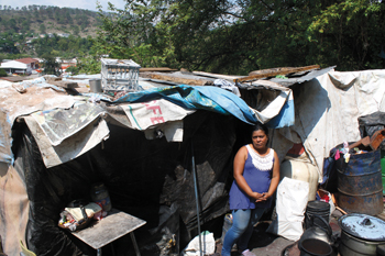 Wendy Carolina Hernández Enríquez stands in front of her home in Tegucigalpa, Honduras, below the city dump where she works. She moved here years ago after she left her abusive husband. Her four youngest children study at the Amor, Fe y Esperanza school. — Jill Steinmetz/MCC