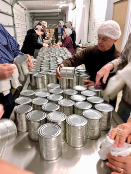 Volunteers prepare cans of chicken for labeling during the Mennonite Central Committee meat canner's visit April 25 in Elmira, Ont. — Rob Patterson