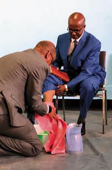 Outgoing MKC President Tewodros Beyene washes the feet of his successor, Desalegn Abede. — Tom Eshleman/LMC