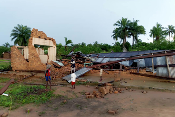 Children from Ndjoko Punda, Democratic Republic of Congo, observe the damage to a Mennonite church caused by the Nov. 22 storm. — Mennonite Mission Network
