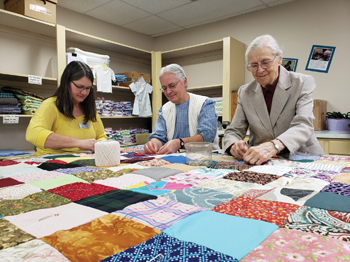 Betsy Kennel, left, Mennonite Central Committee sewing room coordinator of New Holland, Pa., Mary Ann Hershey, center, of Lititz, Pa., and Arlene Kreider, right, of Lititz, Pa., knot a comforter at the MCC East Coast Material Resources Center in Ephrata, Pa., in December. — Diana Voth/MCC