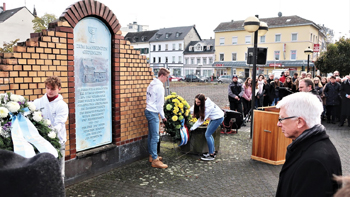 Youth lay wreaths before a memorial sign where a synagogue was destroyed in the Reichs­kristall­nacht (night of broken glass) pogrom of 1938 in Neuwied, Germany. — J. Nelson Kraybill/MWC