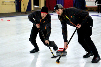 Gerald Heimpel, left, and Reid Kennel sweep a rock on March 5 during the Friars' Briar, an annual Canadian clergy curling tournament held this year in Waterloo, Ont. — Emily McFarlan Miller/RNS