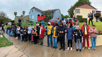 Activists in support of people occupying a vacant home link arms in a barricade as police arrive March 14 in Los Angeles. The occupied home is owned by the California Department of Transportation. — Reclaiming Our Homes