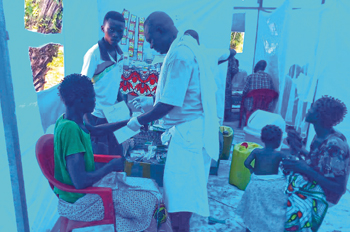 Fernand Muvuma, a nurse from Ndjoko Punda, treats patients in the blue tarp shelters that housed the UMER clinic in March. — Joseph Nkongolo/MMN