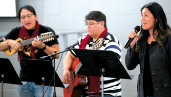 Mariela Sanchez, right, leads singing at Iglesia Menonita Piedra Vida (Living Stone Mennonite Church), a new Hispanic peace congregation in Elkhart, Ind., accompanied by Ramón Tapia, center, and Mauricio Chavez, left. — David Fast/MMN