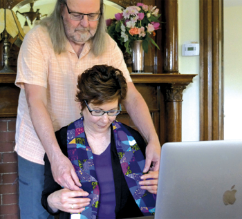 Dan Gallagher places an ordination stole on the shoulders of Community Mennonite Fellowship Pastor Janette Lyndaker Gallagher on May 17 at their home during an online ordination service. — Dan Gallagher