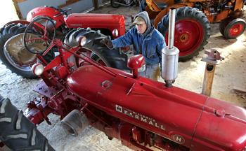 Jerry Toews prepares antique tractors for sale at the 2018 Kansas Mennonite Relief Sale. — Sandra J. Milburn/The Hutchinson News