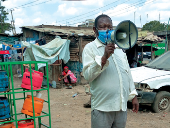 Joseph Mwaura, a community health promoter for Mennonite Central Committee's partner Centre for Peace and Nationhood, uses a megaphone to inform people living in Mathare settlement of Nairobi, Kenya, about signs and symptoms of the coronavirus. He also tells listeners how to prevent the virus from spreading by washing hands and wearing a mask. — Christabel Awuor/CPN