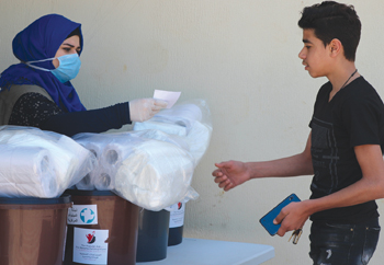 A staff member from the Mennonite Central Committee partner Popular Aid for Relief and Development distributes a COVID-19 hygiene kit May 1 to a community member in Tyre, Lebanon. Recipients are residents of a low-income neighborhood, the majority of whom are Palestinian and Syrian refugees. Names are withheld for security reasons. — Olivia Osley/MCC