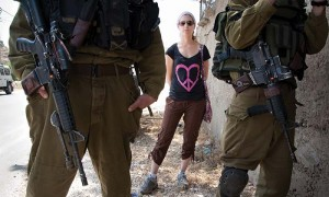 An Israeli solidarity activist with a t-shirt displaying a heart-shaped peace sign stands behind Israeli soldiers during a weekly protest against the Israeli Separation Wall in Al Ma'sara, West Bank, May 18, 2012. If built as planned, the Wall would cut off the village from its agricultural lands.