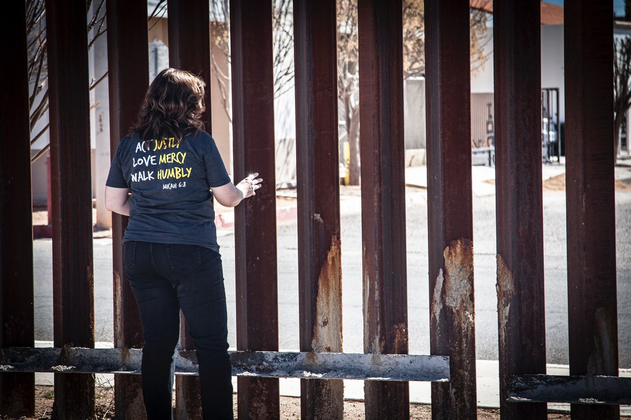 Rhonda Dueck prays at the wall in Douglas, Arizona, on the border between the U.S. and Mexico, as part of a West Coast MCC learning tour desgined to bring attention to faith-based responses to migration, militarization of the border, the effect of the border wall to communities on both sides of the border and the tragedy of migrant deaths. (Photo/James Bergen)