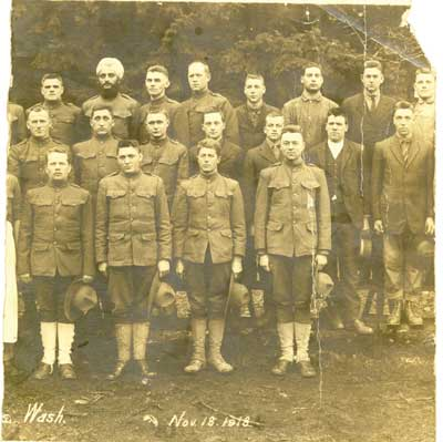 A photograph of conscientious objectors at Camp Lewis, Wash., Nov. 18, 1918. Four known Mennonite men are in the photo: (back row, third from right: Elmer McTimmmonds, lived near Sheridan, Ore.; back row, fourth from right: John Kropf, lived near Harrisburg, Ore.; middle row, fourth from right: Homer Schlegel, lived in Albany, Ore.; middle row, far right: Orie M. Conrad, later lived near Albany, Ore.). Orie refused to train and refused to put on a uniform. He paid dearly for it. At one point he almost lost his life by hanging but an officer saved him and his tormentors were courtmartialed. (Orie M. Conrad Photographs, HM4-384. Mennonite Church USA Archives-Goshen. Goshen, Ind.)