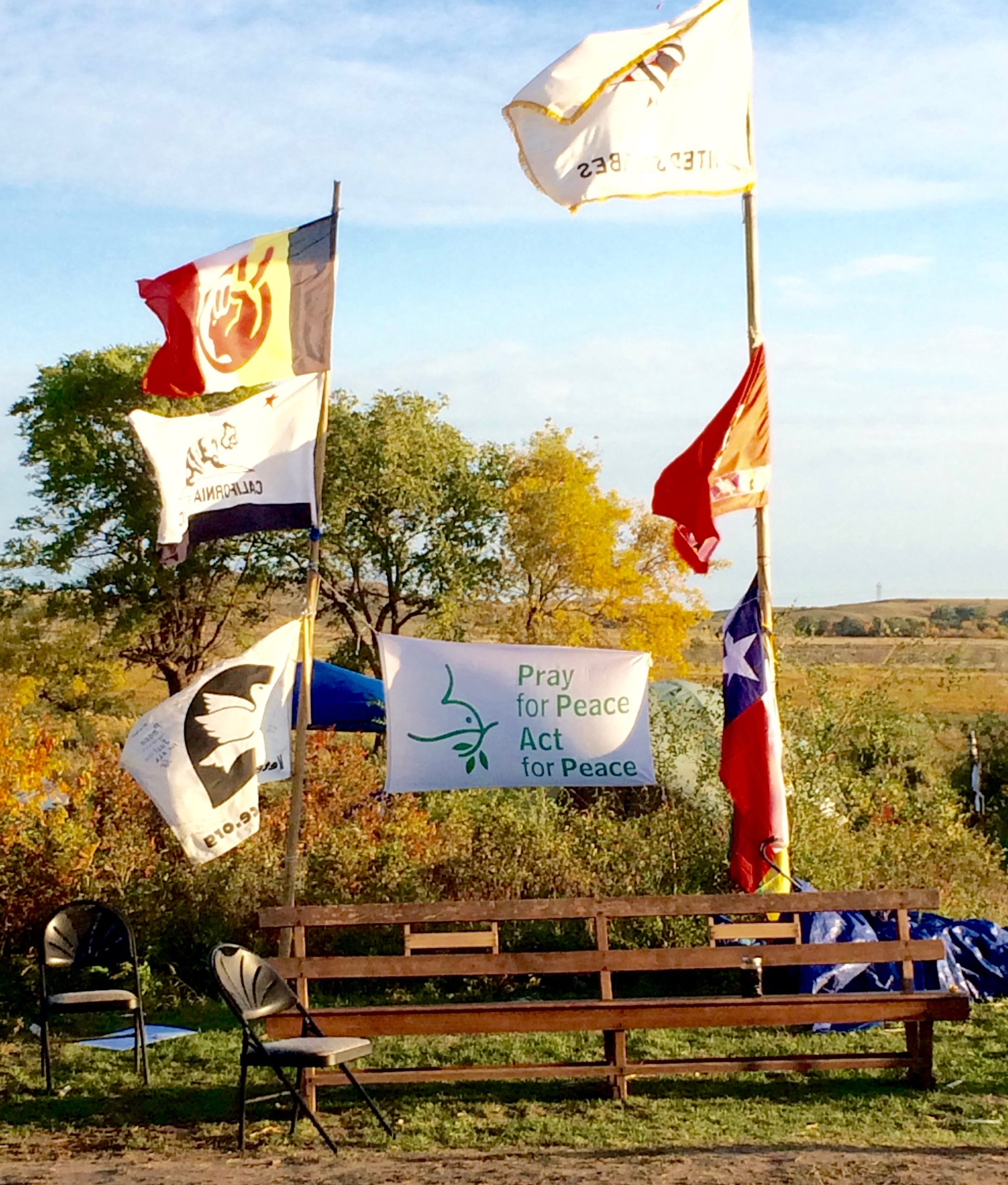 """Some Mennonites must have been at Sacred Stone Camp before us! Among the flags raised there was this """"Pray for Peace, Act for Peace"""" banner. Photo credit: Ken Gingerich"""