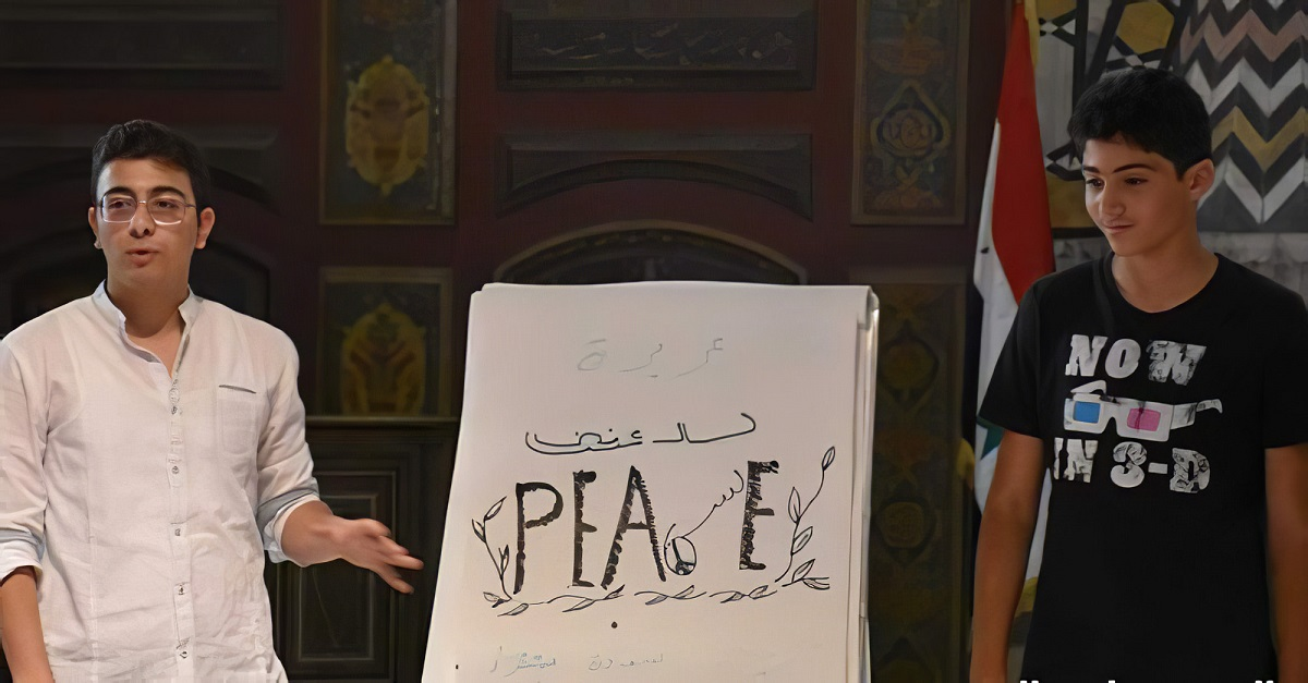 """A presenter (left) with """"Change4Peace,"""" a Syrian civil society organization, stands with a participant during a peace dialogue session in Damascus, Syria, in Fall 2019. Their names and the organization's actual name are withheld for security reasons."""