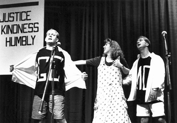 """At the 1992 General Conference Mennonite Church triennial assembly in Sioux Falls, S.D., """"Alice in the Land of Many Knights""""helps Tweedledee and Tweedledum, wearing T-shirts marked """"GC"""" and """"MC,"""" understand they're not so different after all. The GCMC and the Mennonite Church had drawn closer over decades as MCs shed external markers like distinctive clothing, congregations adopted dual affiliations, the denominations began sharing a seminary campus in 1958 and a hymnal in 1969, and members gathered for joint assemblies in 1983 and 1989. — Paul Schrag/MWR"""