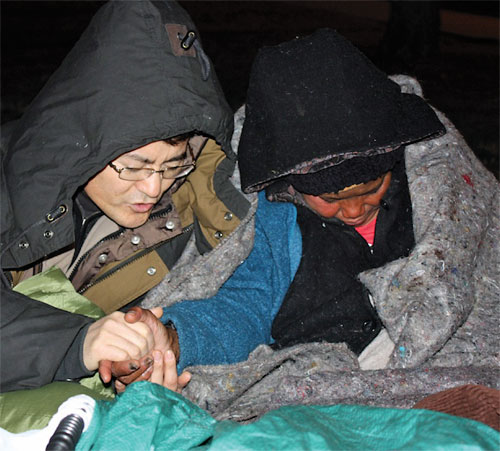 San Jin Choi (left) prays with an individual who is homeless. Photo provided