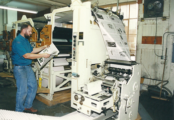 Eldo Wiggers checks papers coming off the press in 2000, the year the company closed its print shop. — Mennonite World Review