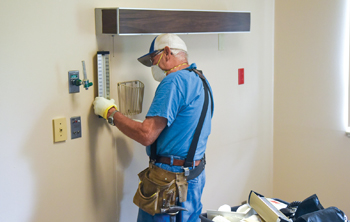 Mennonite Disaster Service project manager Jerry Wyse of Haven, Kan., works with the pressure meter from a sphygmomanometer as part of a project to convert rooms at the former Hillsboro Community Medical Center for use as quarantine housing for Tabor College students. — Michael Klaassen/Tabor College