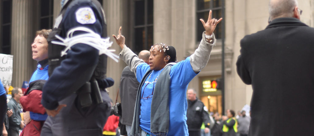 """Woman signing """"I love you"""" after being arrested by police for blocking an intersection as part of nonviolent direct action in Chicago, November 7, 2011"""