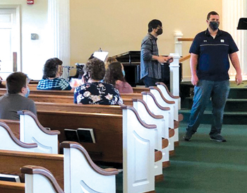 Yellow Creek Mennonite Church usher AJ Newcomer coordinates seating at the Goshen, Ind., congregation's reopening worship service as worship coordinator Sungbin Kim approaches the stage. — Yvonne Pasqualone/Yellow Creek Mennonite Church
